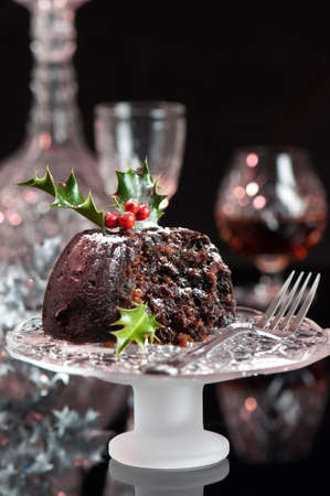 Christmas pudding dusted with icing sugar on glass comport with fork photo