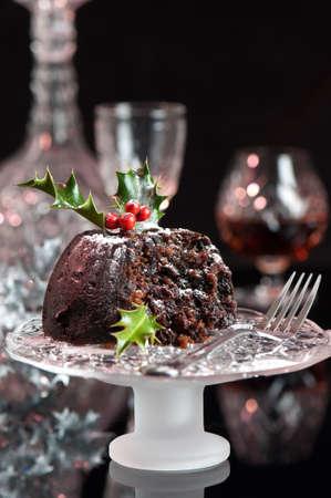 plum pudding: Christmas pudding spolverato con zucchero a velo sulla porta com vetro con forchetta Archivio Fotografico