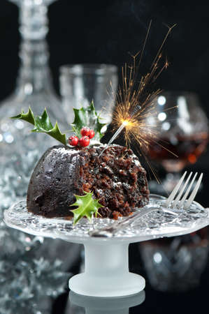 Christmas pudding decorated with lit sparkler in Xmas setting