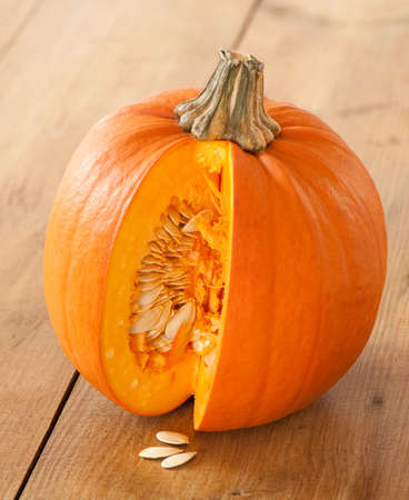 Cut pumpkin on rustic wooden table exposing seeds Stock Photo - 5670180