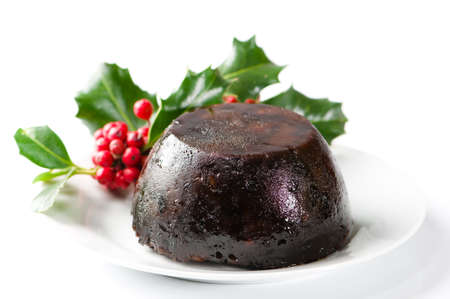 Simple Christmas pudding on white plate and background with holly decoration Stock Photo