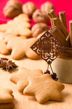 Christmas gingerbread with cinnamon sticks and walnuts in background photo