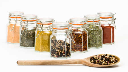 curry spices: Row of spice jars with wooden spoon full of peppercorns on white background