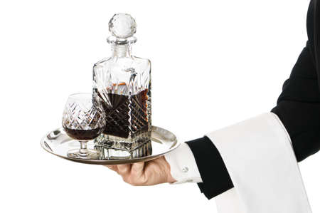 decanter: Waiter serving a glass of brandy with decanter on silver tray Stock Photo