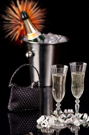 New Year party with glasses of champagne, ice bucket, cocktail bag and fireworks photo