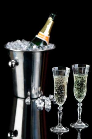 brindis champan: Copas de champ�n espumoso con botella en un cubo de hielo en el fondo