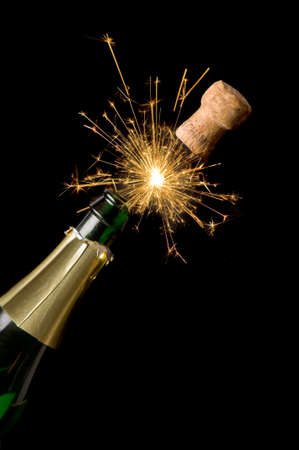 christmas champagne: Champagne bottle and cork with lit firework Stock Photo