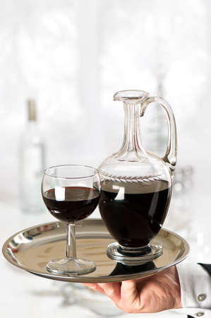 Waiter serving glass of red wine to elegant dinner table photo