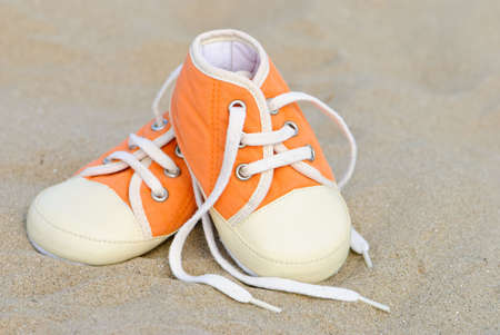 undone: Baby shoes lost in sand on the beach
