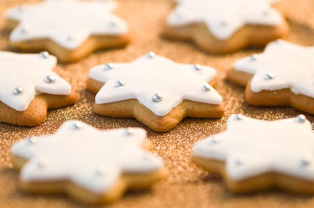Christmas gingerbread stars decorated with white icing on gold background - selective focus on centre biscuit photo