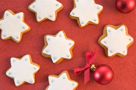 Christmas gingerbread iced stars on red festive background with baubles photo