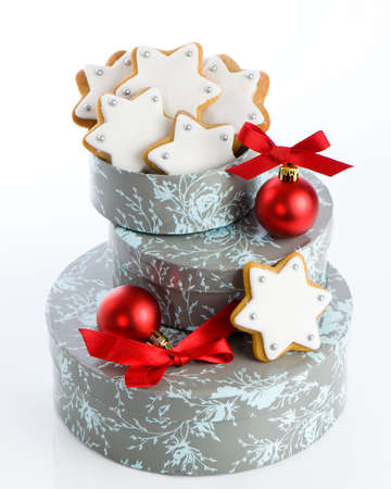 Iced gingerbread stars for Christmas gift with red baubles and ribbons photo