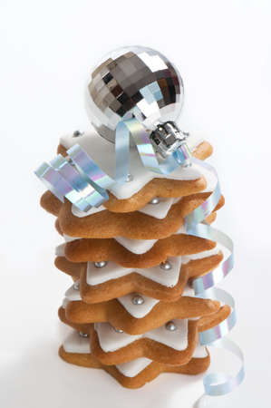 Stack of Christmas gingerbread cookies with silver bauble and ribbon on white background photo