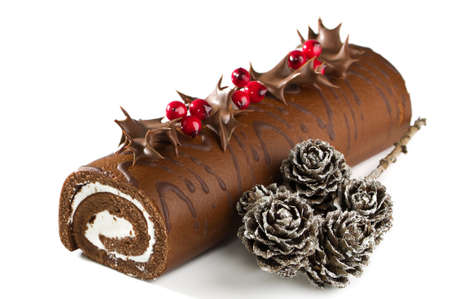 swiss roll: Christmas chocolate yule log with holly, berries, and pine cones