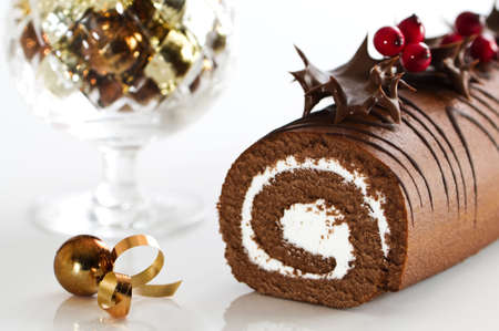 weihnachtskuchen: Schokolade Jules-Log Weihnachtskuchen dekoriert mit Schokolade-beschichteten-stechpalme und Beeren