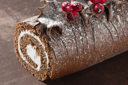 dipped: Close up of Christmas Yule chocolate log decorated with dipped holly leaves and berries, dusted with icing sugar
