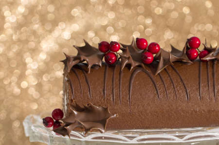 yule log: Festive Christmas roulade on glass cake stand decorated with chocolate dipped holly leaves and berries - gold bokeh background Stock Photo