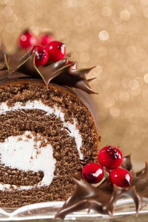 weihnachtskuchen: Abschnitt der Schokolade Weihnachtskuchen dekoriert mit Abblendlicht stechpalme Bl�tter und gold Bokeh-Hintergrund  Lizenzfreie Bilder