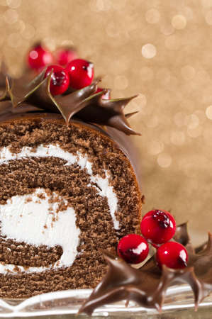 swiss roll: Section of chocolate Christmas cake decorated with dipped holly leaves  and gold bokeh background
