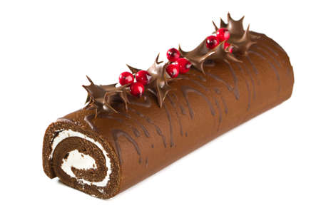 Christmas yule log  cake decorated with chocolate dipped holly leaves and berries on white background