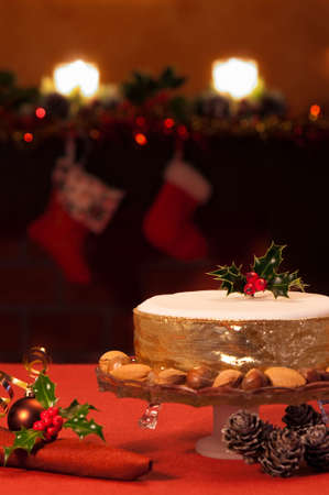 christmas pudding: Christmas cake on festive table with fireplace in background Stock Photo