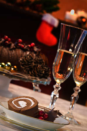 Serving of chocolate swiss roll with champagne in artistic Christmas setting photo
