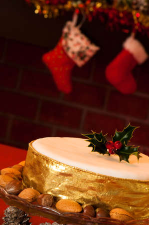 Close up of Christmas cake in festive setting with fireplace in background photo