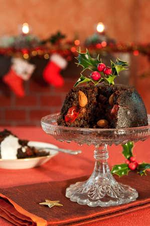 camino natale: Budino di Natale decorato con agrifoglio e bacche in ambiente festoso con camino in background