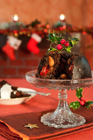candlelit: Christmas pudding decorated with holly and berries in festive setting with fireplace in background