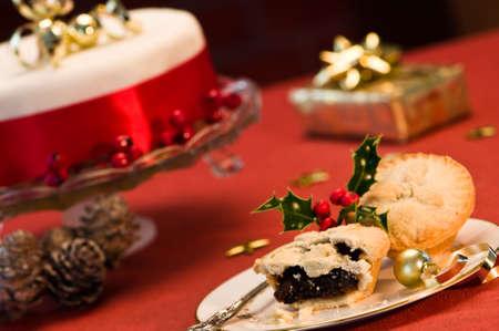 carne picada: Empanadas de picadillo de Navidad con pastel y presente en segundo plano
