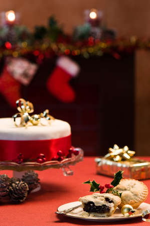 Festive table setting with Christmas cake and mince pies, decorated fireplace in background with lit candles photo