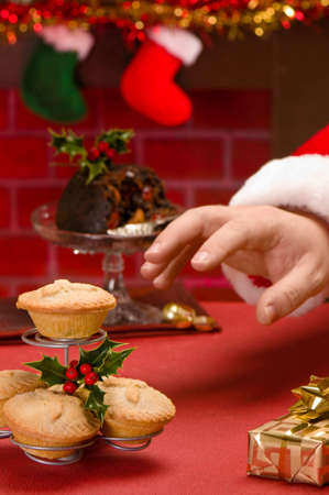 minced pie: Santa Claus on Christmas eve reaching for a mince pie Stock Photo