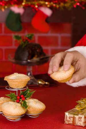 Santa Claus takes a mince pie left for him on Christmas eve, decorated fireplace in background photo