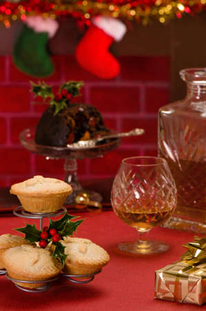 Christmas food with glass and decanter of brandy and gift with fireplace in background photo