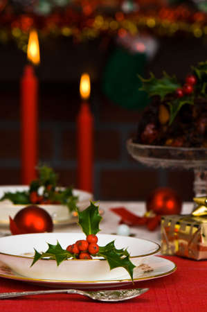 christmas pudding: Festive Christmas table setting with lit candles and fireplace in background