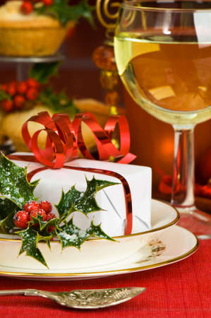 Christmas table setting with gift, decorations and glass of wine photo