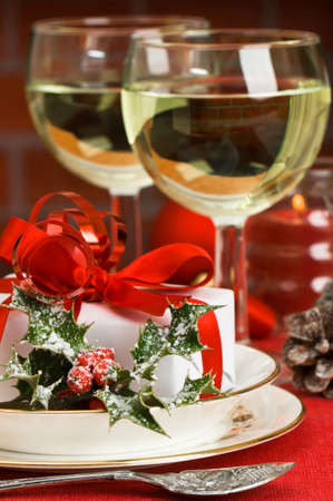 Table setting with gift and white wine ready for Christmas day photo