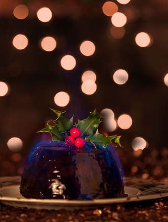 christmas pudding: Flaming Christmas pudding with blue flame, fairy lights in background