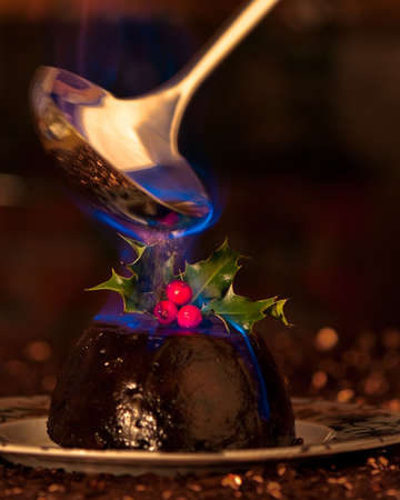 blue flame: Burning Christmas pudding with ladle of brandy spirit, focus on holly and motion blur on ladle