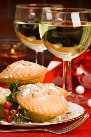 Christmas mince pies with glasses of white wine and decorated gift in background with lit candle photo