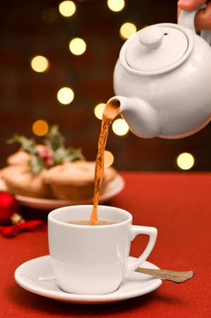 mince: Cup of tea being poured at Christmas time with plate of mince pies in background