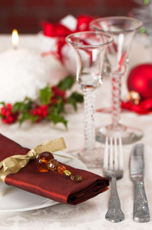 white napkin: Christmas table setting with focus on napkin jewel and lit candle in background