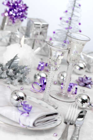 Angled festive Christmas holiday table setting with silver and purple theme, focus on stem of antique wine glass photo