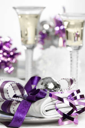 Purple Christmas table setting with napkin and glasses of white wine  photo