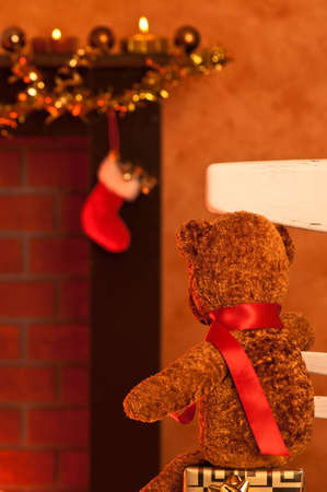 Little teddy bear toy waits for Santa Claus on a chair by the fireplace on Christmas eve photo