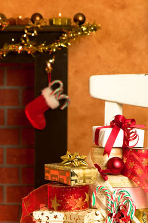 Wrapped Christmas presents on rustic chair in front of festive fireplace Stock Photo - 5866261