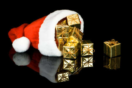 Santa hat overflowing with gold presents on black background with reflection photo