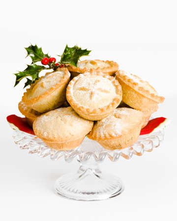 Glass comport of freshly baked mince pies for Christmas decorated with holly and berries photo