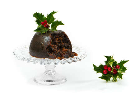 plum pudding: Christmas pudding on glass comport with holly and berries decoration