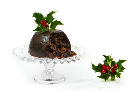 pudin: Christmas pudding sobre vidrio entra�en con decoraci�n de acebo y bayas  Foto de archivo